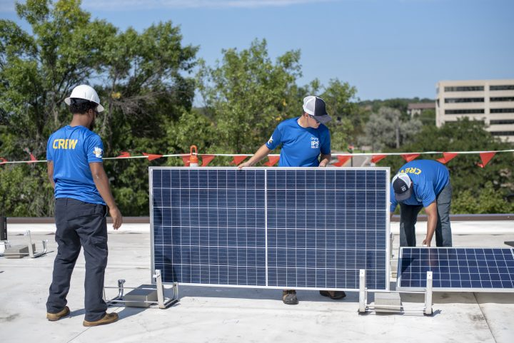 impact power solutions workers installing solar panels on rooftop