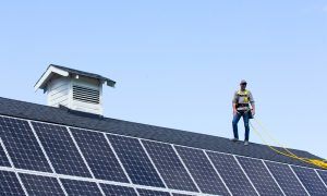 all energy solar worker on rooftop